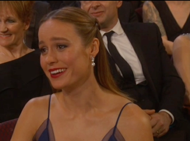 Brie Larson reaccionando, como podía, al monólogo inicial de Chris Rock.