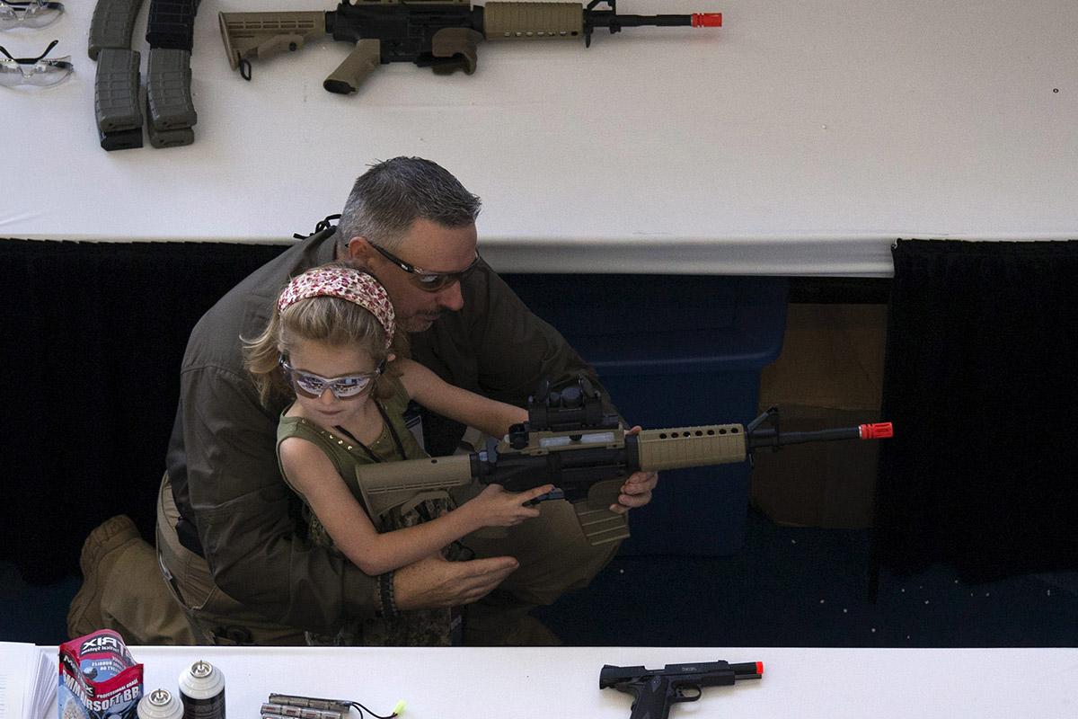 Un hombre enseña a su hija a manejar el arma en el 'Día de la Juventud' de la NRA.