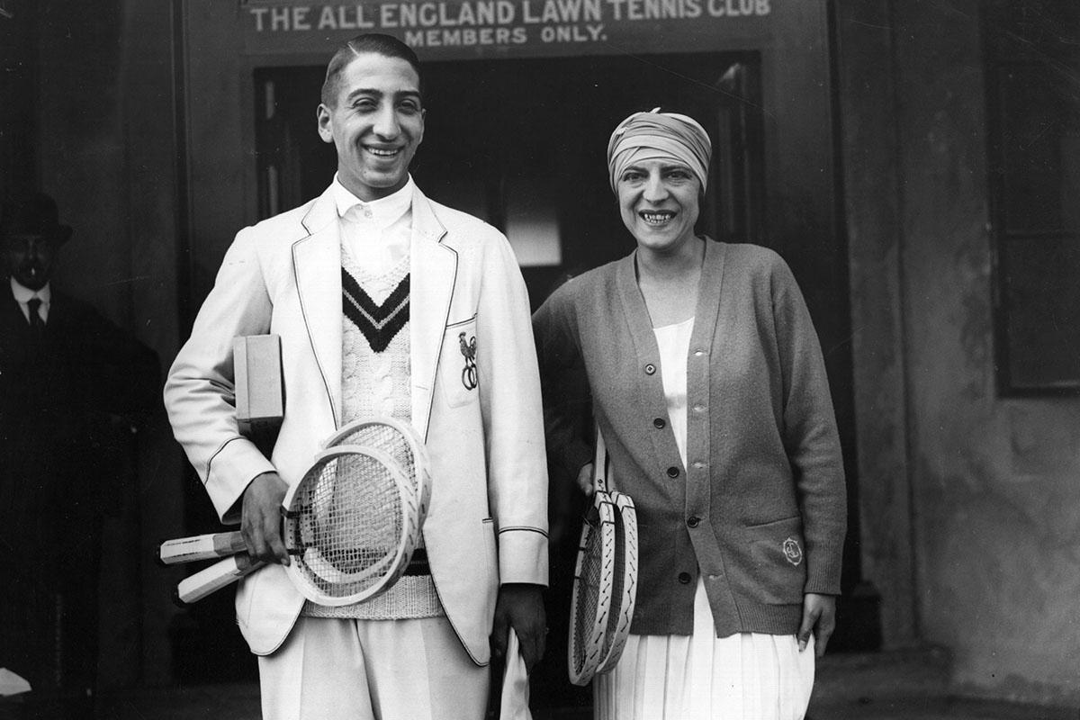 Suzanne Lenglen, vestida con cardigan, acompañada del también tenista René Lacoste.