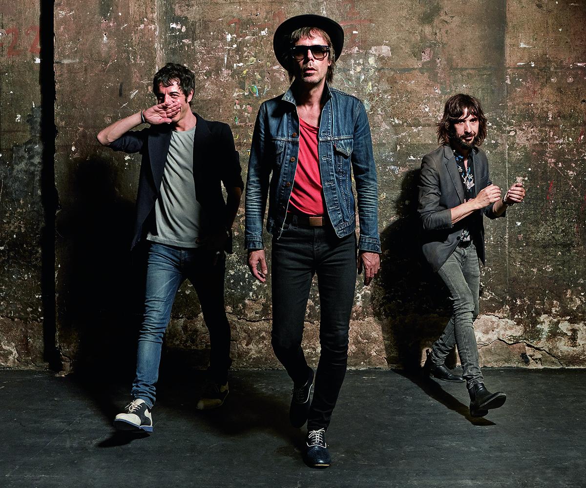 De izquierda a derecha, Marc Ros (cantante, guitarra y bajo) viste chaqueta vintage, camisa de SHAH SAFARI, pantalón de Nudie Jeans y botines de H&M. Jesús Senra (segundas voces, bajo, sitar y guitarras eléctrica y acústica), con camiseta de H&M, pantalón de LEVI'S, zapatos de LOUBOUTIN y sombrero de ONTOP. Axel Pí (batería, tablas y bongos) lleva chaqueta vintage, pantalón de NUDIE JEANS y zapatos de MARATTI.